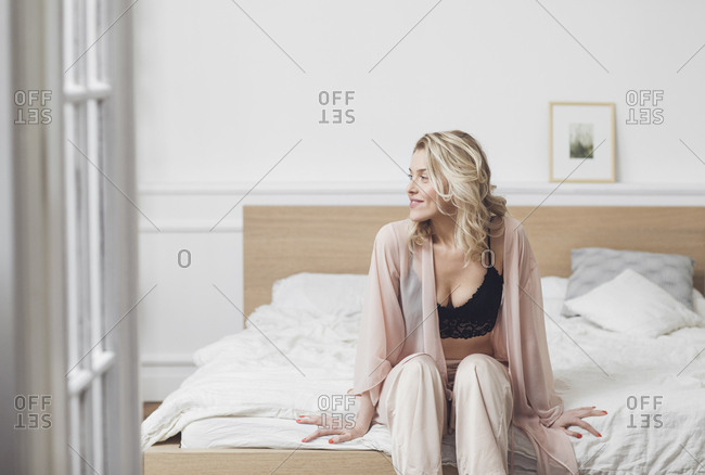 Portrait of beautiful blonde Caucasian woman sitting on her bed in lingerie