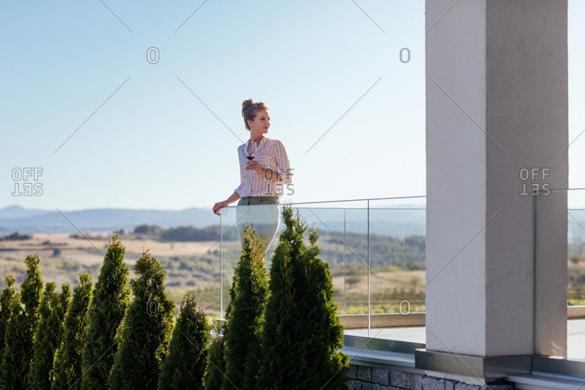 Portrait of beautiful smiling woman drinking wine and standing on terrace