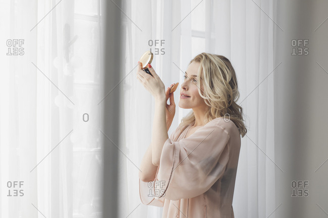 Beautiful blonde Caucasian woman putting make up on and standing by the window in morning