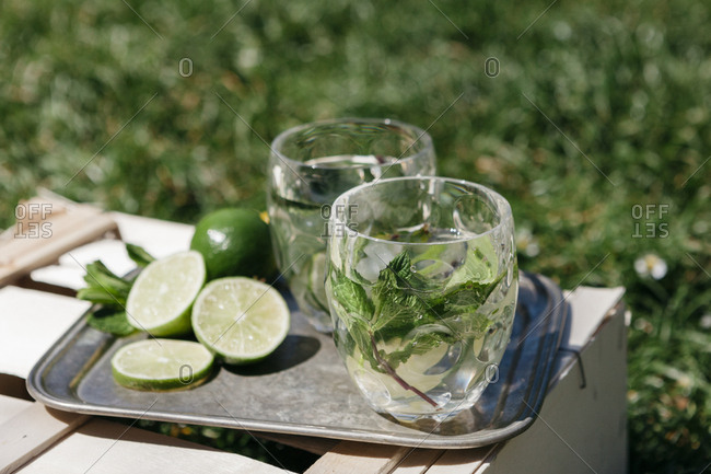 Drinks made with mint leaves and lime served on wooden crate