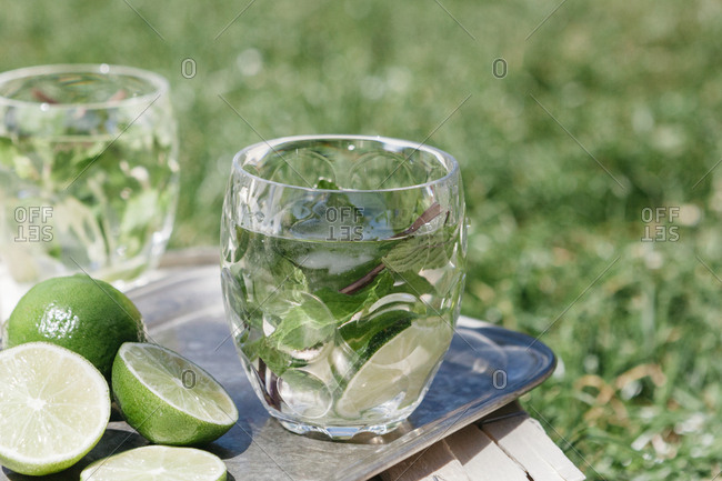 Drinks made with limes and mint leaves served outdoors