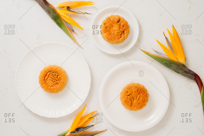 Vietnamese Mid-Autumn Festival moon cakes with tropical bird of paradise flowers