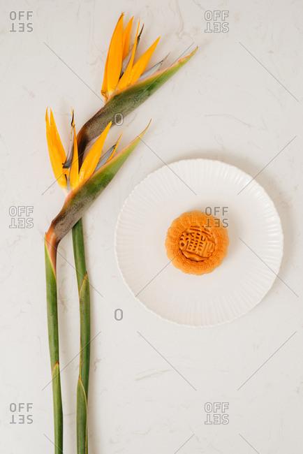 Vietnamese Mid-Autumn Festival moon cake with bird of paradise flowers