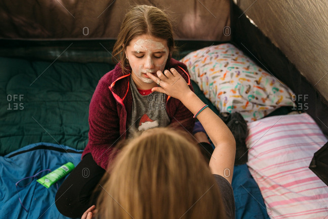 Girls applying facial masks inside camping tent