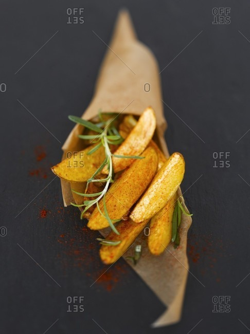 Potato wedges with paprika & rosemary in baking parchment cone