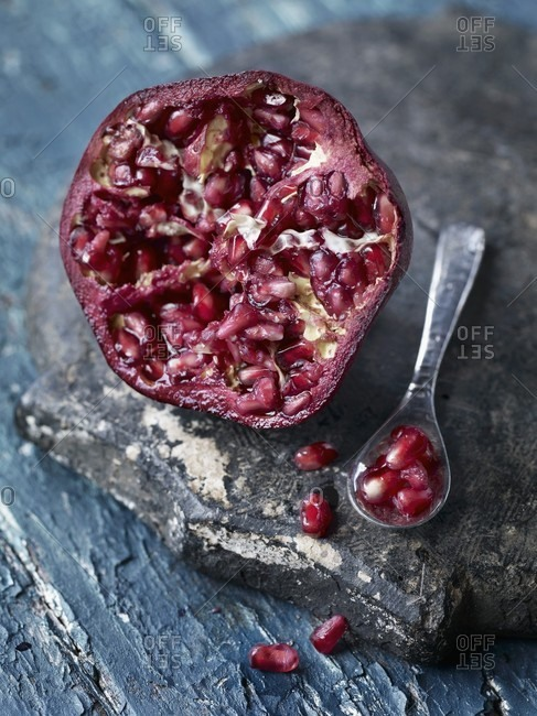 Half a pomegranate with a spoonful of seeds next to it