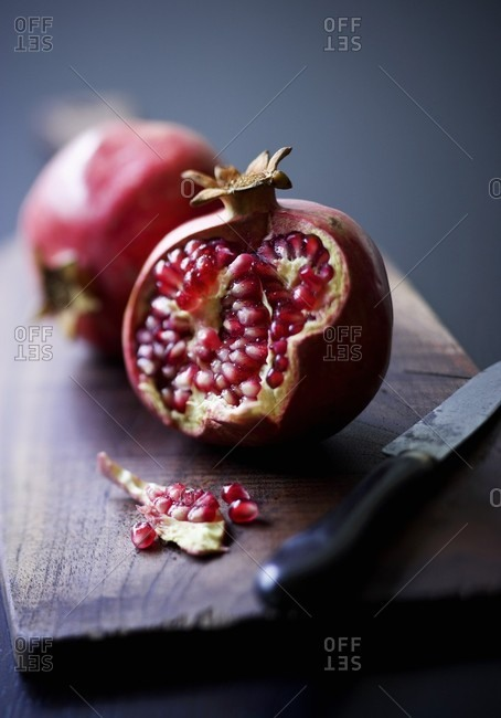 A pomegranate which has been broken open on a wooden board