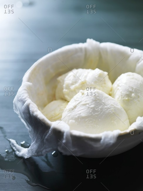 Mozzarella in a bowl lined with a muslin cloth