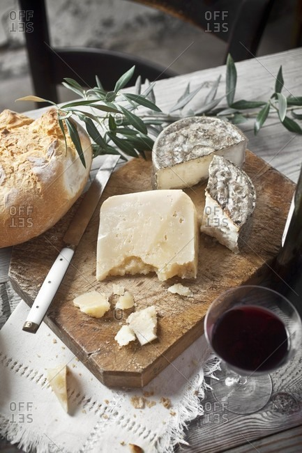 Manchego cheese and goat's cheese on a wooden board with bread and red wine