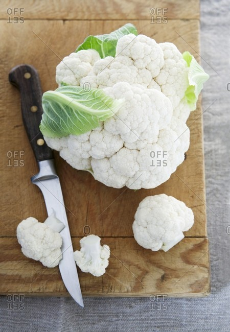 Cauliflower and a knife on a chopping board