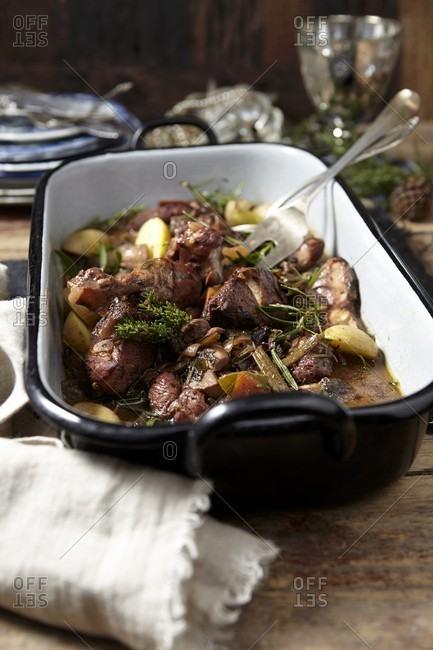 Coq au vin in a roasting tin