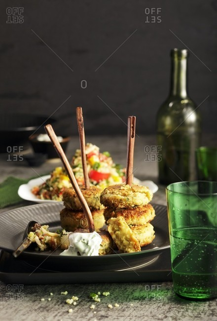 Falafel skewers with sesame seeds, dip and tabbouleh