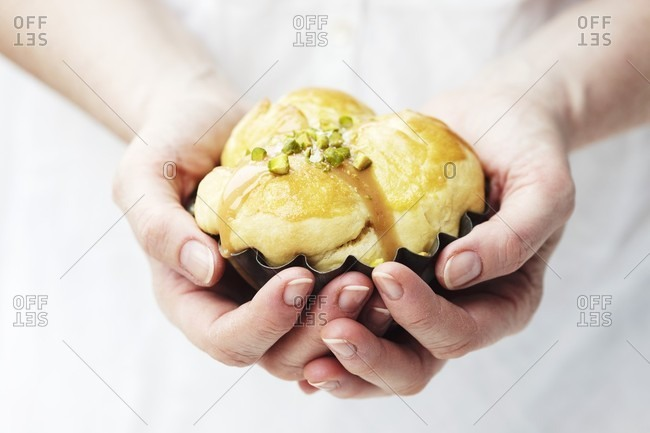 A woman's hands holding a brioche with caramel sauce and pistachios