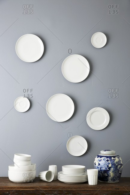 Stacked, simple china crockery and patterned, lidded urn below white plates on grey wall