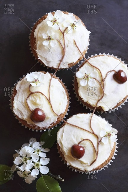 Cupcakes decorated with cherries and cherry blossom arranged to form a tree