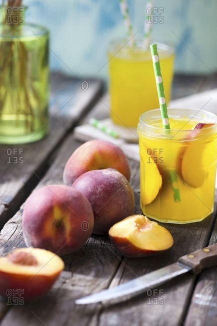 Peach juice and fresh peaches on a wooden table