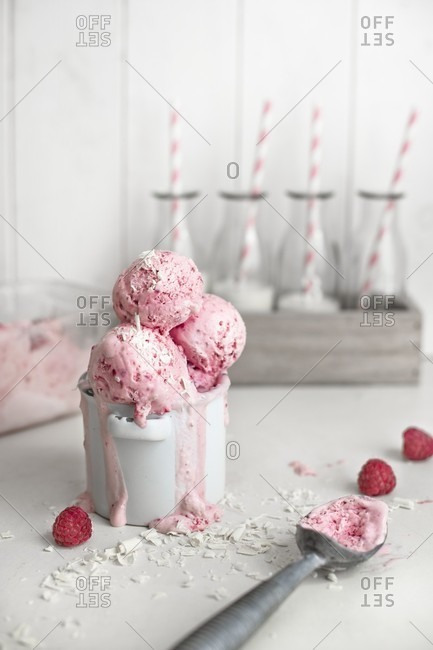 Frozen raspberry yogurt with grated white chocolate in a pot with mini bottles of milk in the background