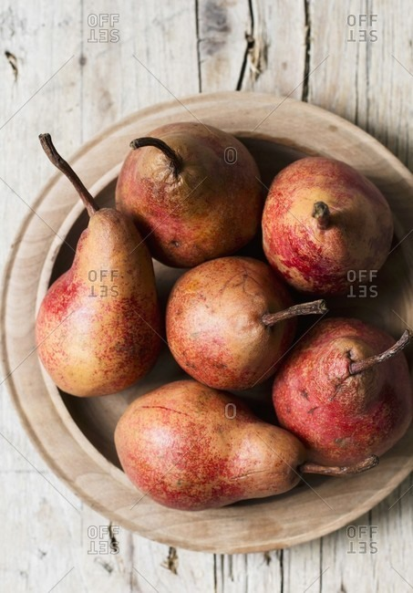 Red pears in a wooden bowl (seen from above)