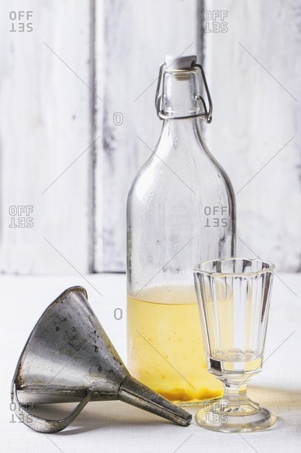 A bottle of homemade liqueur with a vintage glass and a funnel
