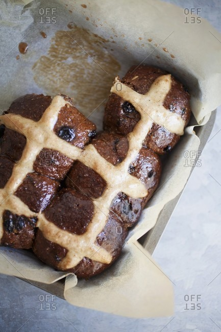 Hot cross buns in a baking tin lined with parchment paper