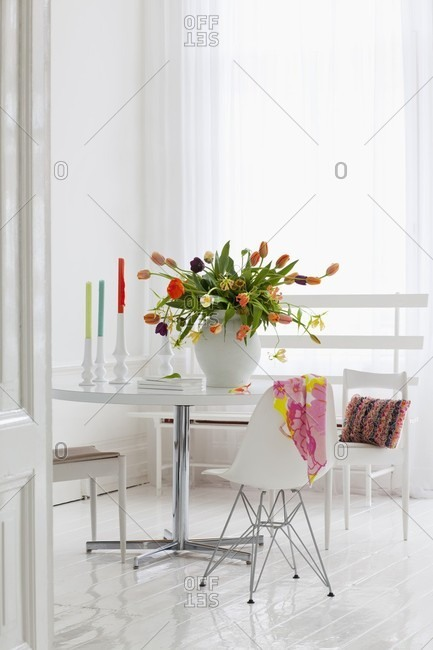 Luxuriant bouquet of multicoloured tulips on dining table in white interior