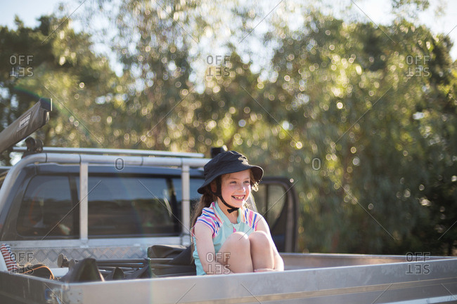 Smiling girl sitting in back of the ute waiting to go to the beach