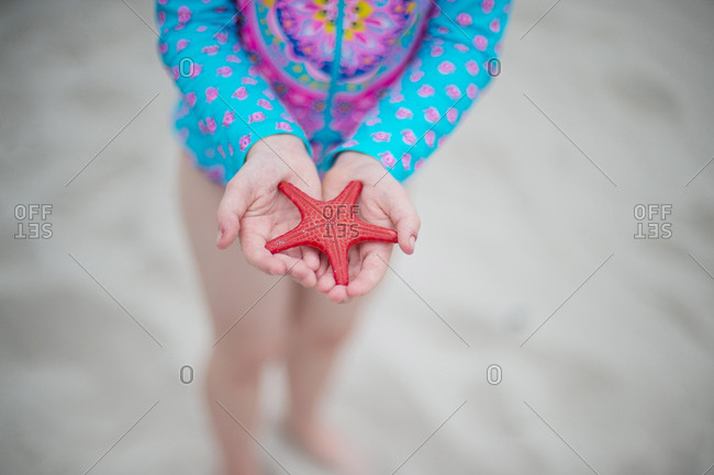 Girl holding red starfish at the beach
