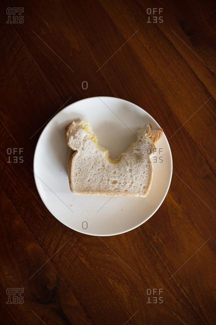 Half-eaten sandwich on plate on table