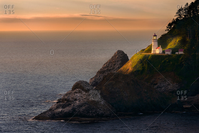 Heceta Lighthouse briefly illuminated by setting Sun.