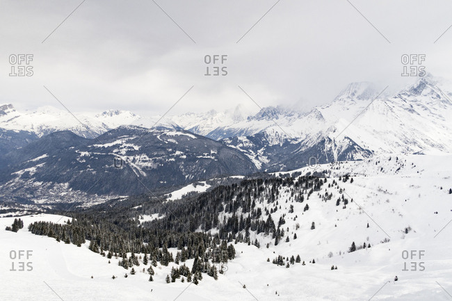Snow-covered mountains in the forest of the French Alps