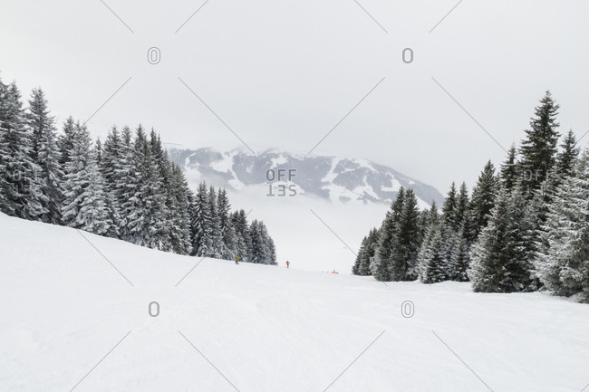 Two skiers going down in a mountain in the Alps