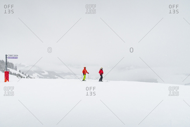 Two skiers on a snow-covered mountain in the Alps