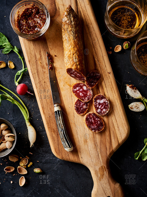 Sliced sausage and homemade mustard on a cutting board with nuts and herbs