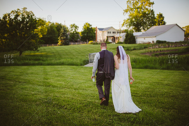 Bride and groom walking away together at outdoor farm wedding