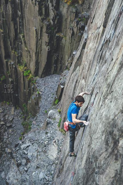 Rock climber ascending slate cliff at Dinorwic Slate Quarry in Llanberis, Snowdonia, UK