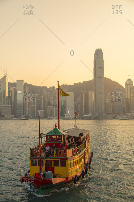 Hong Kong, China - March 11, 2018: Tour boat in Victoria Harbour at sunset