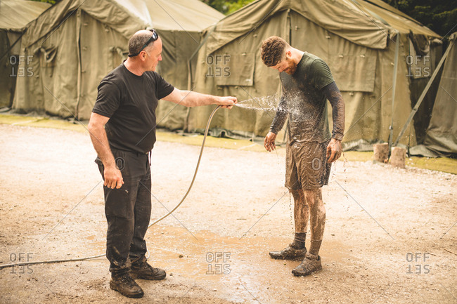 Trainer washing mans face with water at boot camp