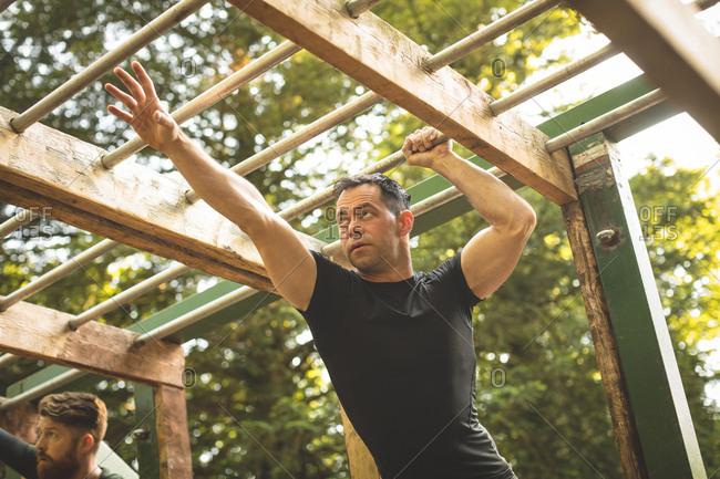 Fit man climbing monkey bars at boot camp
