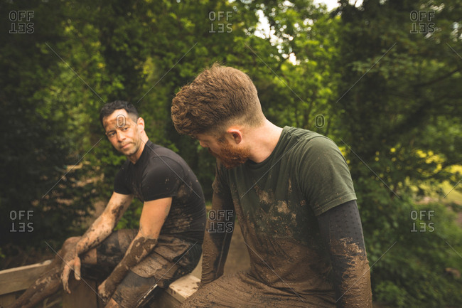 Fit men relaxing over obstacle course at boot camp