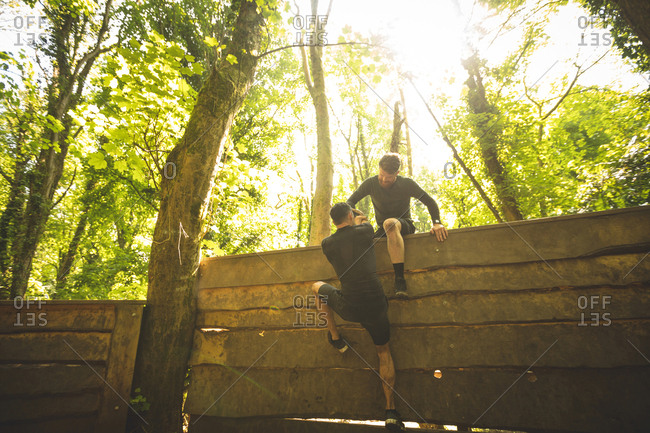 Fit man assisting his teammate to climb a wooden wall at boot camp