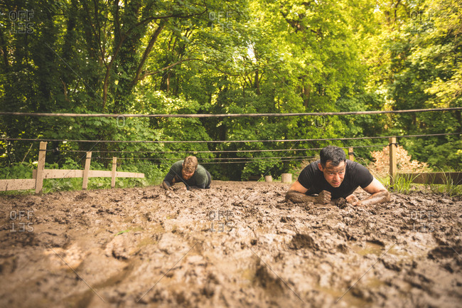 Fit men training under obstacle course at boot camp