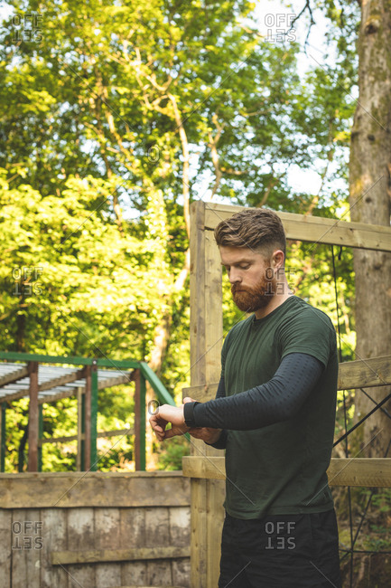 Fit man using smartwatch at boot camp on sunny day