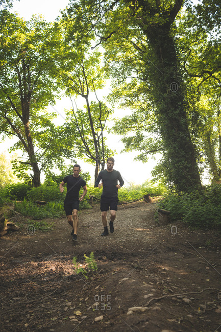 Two men jogging together at boot camp on a sunny day