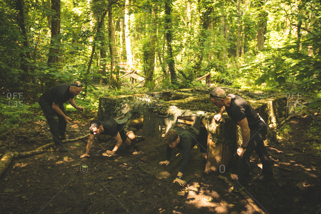 Fit men crawling under the net during obstacle course at boot camp