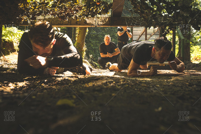 Fit men crawling under the net during obstacle course at boot camps