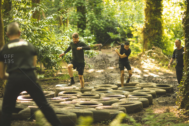 Fit men training over tires obstacle course at boot camp