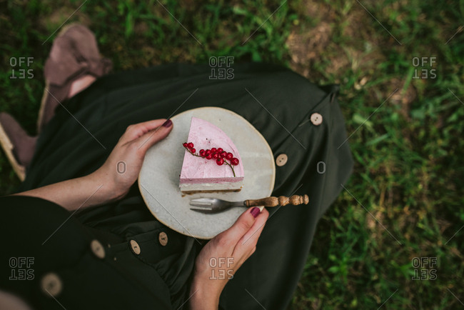 Woman eating a slice of cake with berries