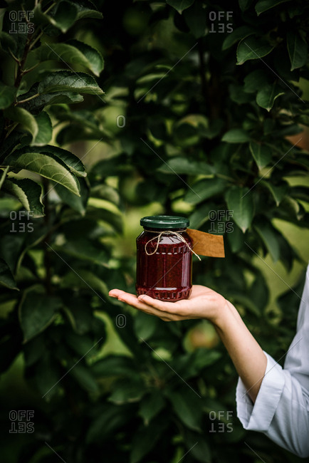 Woman holding jar of jelly with blank label