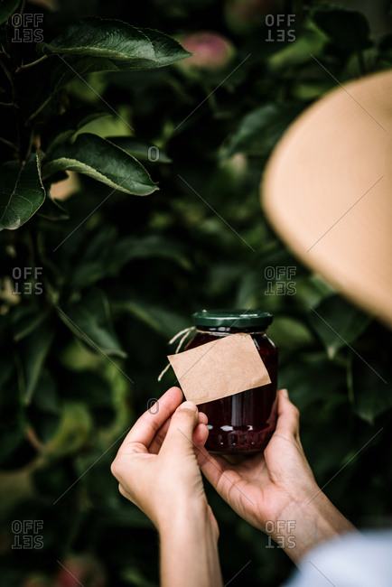 Woman holding jar of jam with blank label