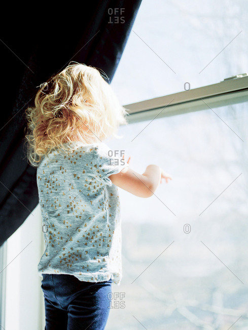 Little blonde girl looking out a window